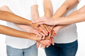 cropped view of four multicultural women putting hands together isolated on white