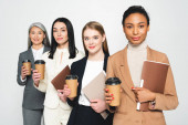 four happy and multicultural businesswomen holding folders and paper cups isolated on white