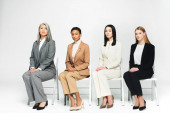 multicultural businesswomen in suits sitting on chairs and looking at camera on white