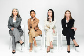 four multicultural businesswomen in suits sitting on chairs and looking at camera on white
