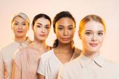 szelektív fókusz boldog multikulturális nők nézi kamera elszigetelt bézs