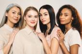 schöne multikulturelle Frauen, die isoliert auf weiß in die Kamera schauen