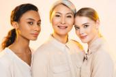 három gyönyörű multikulturális nők mosolyogva elszigetelt bézs