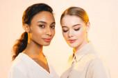Fényképek két vonzó multikulturális nők smink elszigetelt bézs