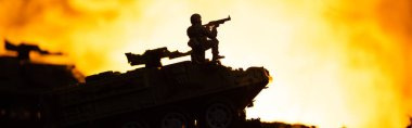 Battle scene with silhouette of toy soldier on tank with fire at background, panoramic shot