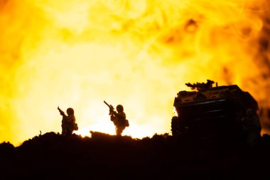 Battle scene with silhouettes of toy tank and soldiers with fire at background