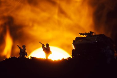 Silhouettes of toy warriors and tank on battleground with sunset and fire at background stock vector