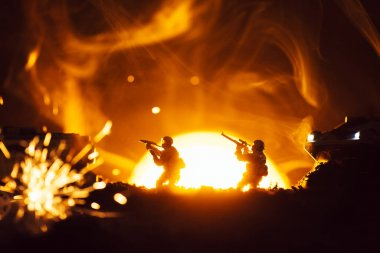 Selective focus of toy warriors with tanks near explosion and smoke with sunset at background
