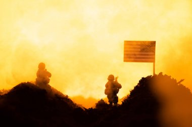 Battle scene with toy soldiers near american flag with fire at background