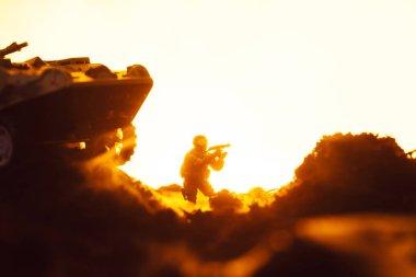 Battle scene with toy soldier near tank on battleground on yellow background