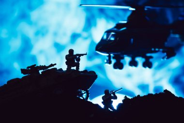Scene of battle with toy warriors, tank and helicopter with smoke on blue background