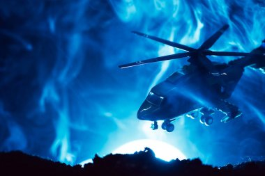 Battle scene with toy helicopter in smoke with moon on blue background