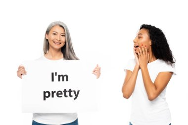 cheerful african american and asian women near i`m pretty placard isolated on white