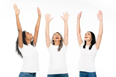 Happy multicultural women with hands above head looking up isolated on white stock vector