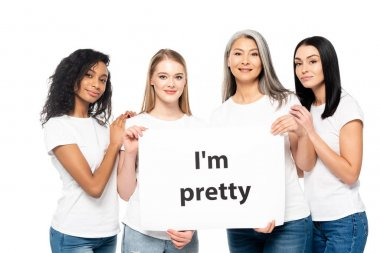 cheerful multicultural women near placard with i`m pretty lettering isolated on white