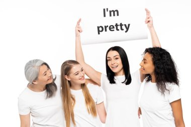 four multicultural women near placard with i`m pretty lettering isolated on white