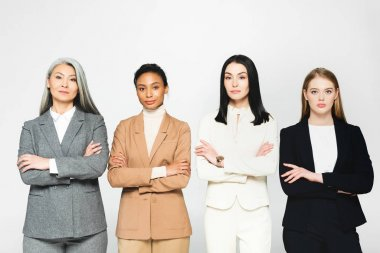 multicultural businesswomen in suits standing with crossed arms isolated on white