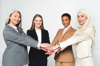 Multicultural businesswomen putting hands together isolated on white stock vector