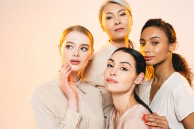 beautiful multicultural women with makeup isolated on beige