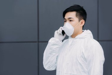 Asian epidemiologist in hazmat suit and respirator mask talking on smartphone and looking away outside stock vector