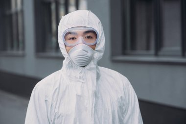Asian epidemiologist in hazmat suit and respirator mask looking at camera while standing near building stock vector