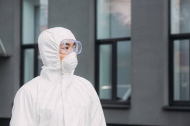 Asian epidemiologist in hazmat suit and respirator mask looking away while standing near building stock vector