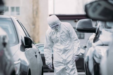 Selective focus of asian epidemiologist in hazmat suit and respirator mask inspecting vehicles on parking lot stock vector