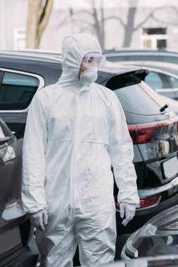 Asian epidemiologist in hazmat suit and respirator mask inspecting cars on parking lot stock vector