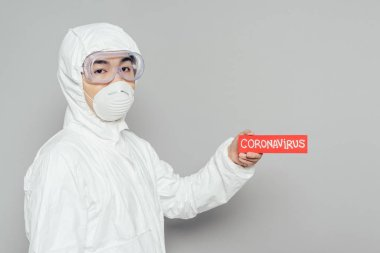 Asian epidemiologist in hazmat suit and respirator mask holding warning card with coronavirus inscription on grey background stock vector