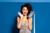 schockiert schöne afrikanisch-amerikanische Frau in silbernem Kleid hält Terminal mit Karo auf blauem Hintergrund