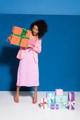 elegant lächelnde afrikanisch-amerikanische Frau in der Nähe von Geschenken auf blauem Hintergrund