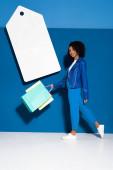 afrikanisch-amerikanische Frau, die mit Einkaufstaschen in der Nähe großer leerer Preisschilder auf blauem Hintergrund spaziert