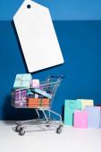 nákupní tašky, vozík s dárky a velký prázdný ceník na modrém pozadí