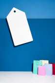 colorful shopping bags and big blank price tag on blue background