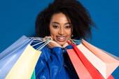 usmívající se africká americká žena s rovnátka a nákupní tašky izolované na modré