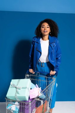 smiling african american woman with shopping cart full of gifts on blue background
