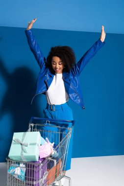 happy african american woman with hands in air and shopping cart full of gifts on blue background