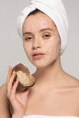 Fotografie schönes Mädchen mit Handtuch auf dem Kopf, Kokosnussschale mit Peeling, isoliert auf grau