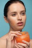 beautiful girl applying yellow sugar scrub from plastic container, isolated on blue