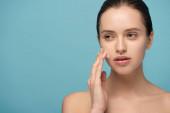 gyönyörű fiatal nő alkalmazása tisztító hab az arcon, elszigetelt kék