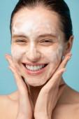 krásná usmívající se mladá žena nanášení čistící pěny na obličej, izolované na modré