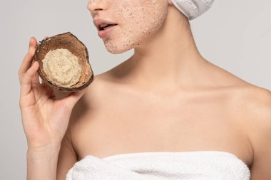 cropped view of girl with towel on head holding coconut shell with scrub, isolated on grey