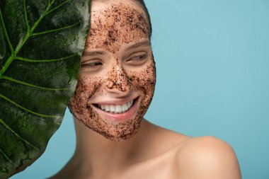 Smiling young woman with coffee scrub on face, isolated on blue with leaf stock vector