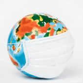 close up of globe in medical mask on white