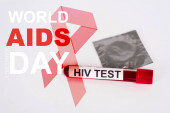 sample with hiv test, condom in pack and world aids day lettering near red ribbon illustration on white