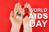 vrchní pohled na ženu drží červenou stuhu a pilulky v blízkosti světových pomůcek den nápis na červenou