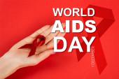 levágott kilátás nő kezében piros szalag közel világ AIDS nap felirat piros