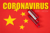 Photo top view of samples with coronavirus test and coronavirus, 2019-ncov lettering near red chinese flag