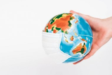 Cropped view of man holding globe in protective mask isolated on white stock vector