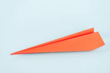 Orange paper plane on blue with copy space stock vector